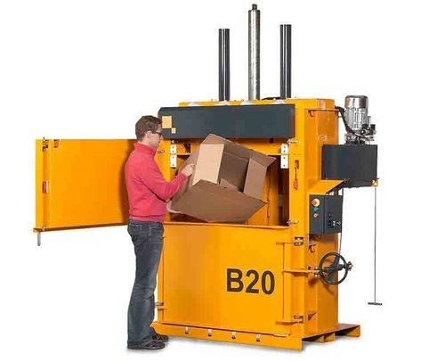 A man putting cardboard box in the baler
